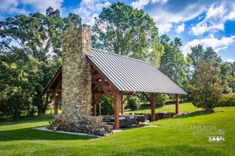 grand teton timber frame pavilion with a large fireplace and chimney