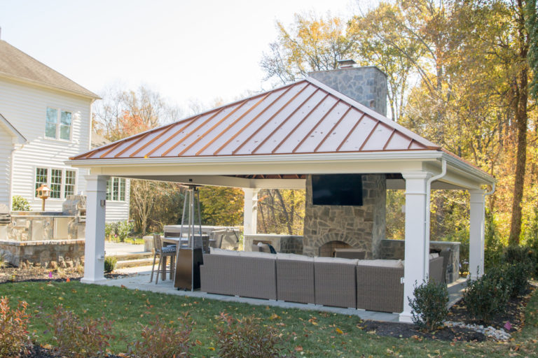 24×24 carbbean vinyl pavilion with red metal roof and a fireplace