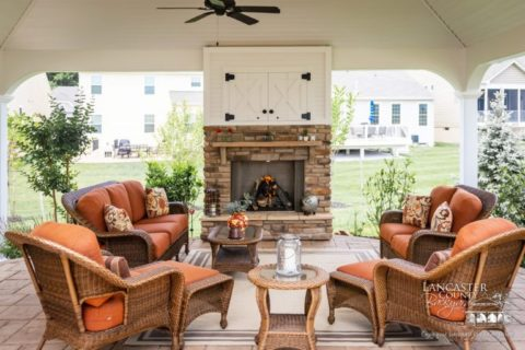 outdoor fireplace under pavilion with couches