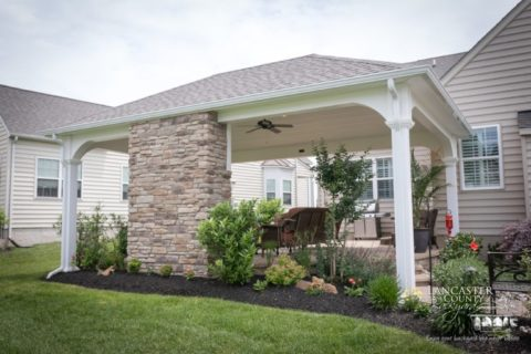 outdoor fireplace under pavilion with flowerbed