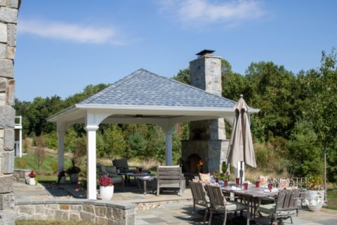 dining table and outdoor fireplace under pavilion