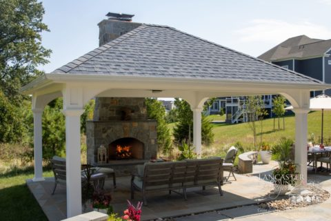fire in outdoor fireplace under pavilion
