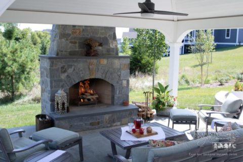fire burning in outdoor fireplace under pavilion