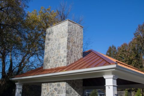 chimney through roof in outdoor fireplace under pavilion