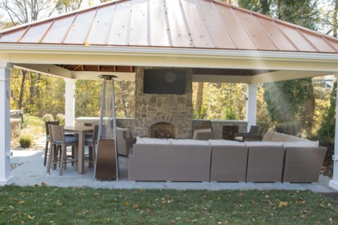 hangout area in outdoor fireplace under pavilion