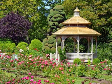 A Beautiful Permanent Vinyl Gazebo In The Backyard With Some Red and Pink Flowers Around It